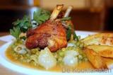 Kippenboutjes met witbier, goud gebakken aardappelen en erwten op zijn Frans